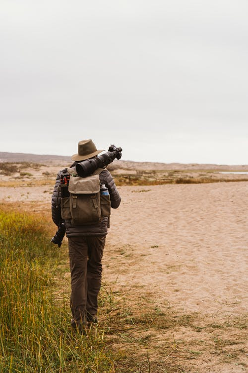 Back View Of Person Carrying Camera Equipment Walking on Sandy Ground