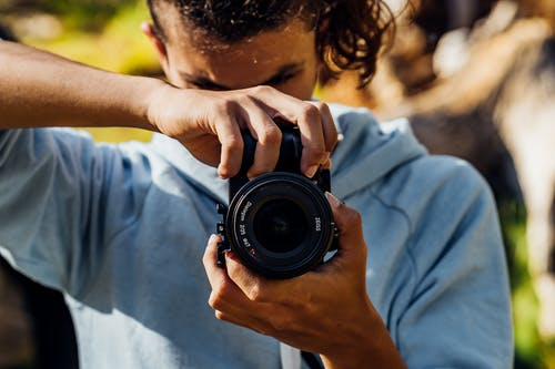 A Young Man Using A Black Dslr Camera