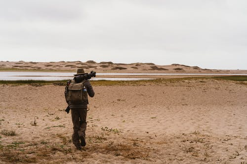 Man Walking With A Backpack And Camera Equipment On Sandy Ground