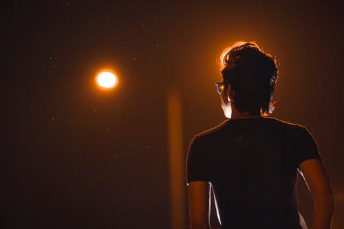 Back View Photo of Man in Glasses Posing During Night