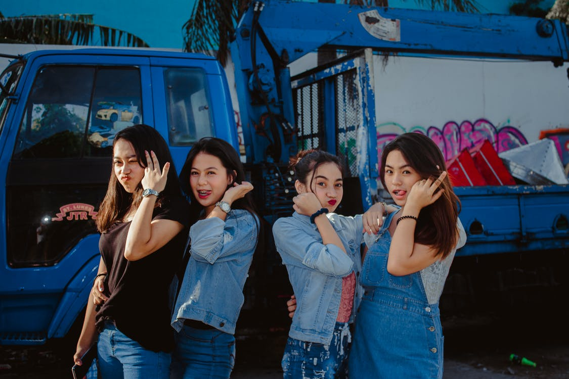 Young Women In Casual Wear Standing In Front Of A Truck