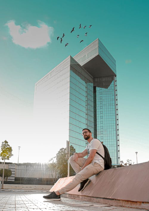 Man Sitting Beside Mirror Building