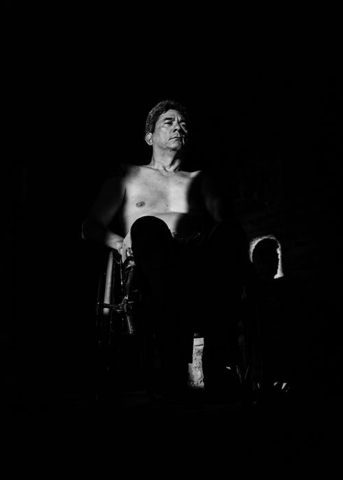 Grayscale Photography of Topless Man Sitting