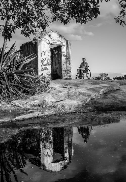 Grayscale Photography of Person Sitting on Wheelchair Near Pond