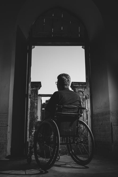 Grayscale Photography of Man Sitting on Wheelchair