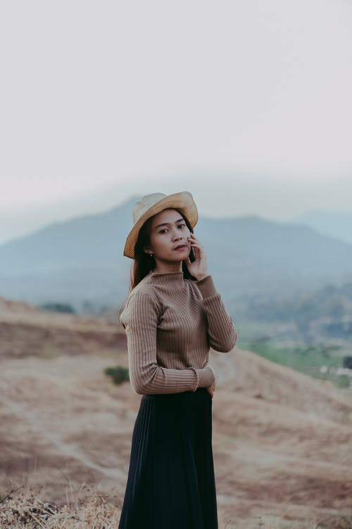 Woman Wearing Brown Long Sleeved Top And Hat