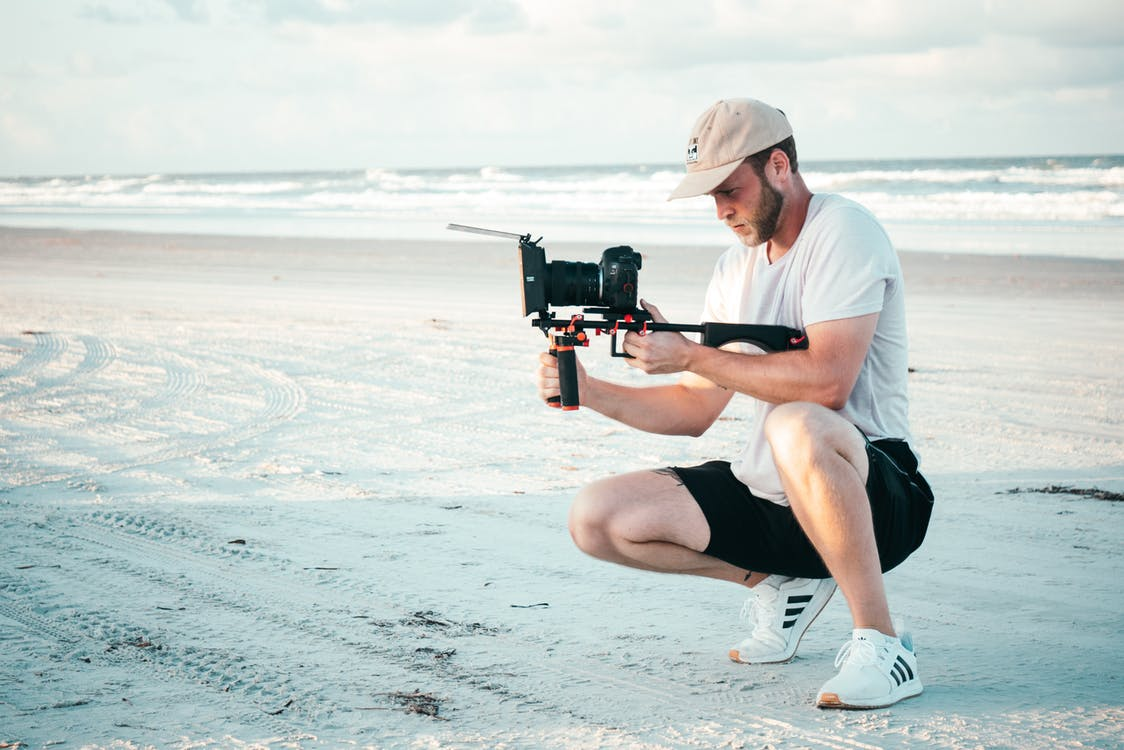 Man Holding Black Dslr Camera Outdoors