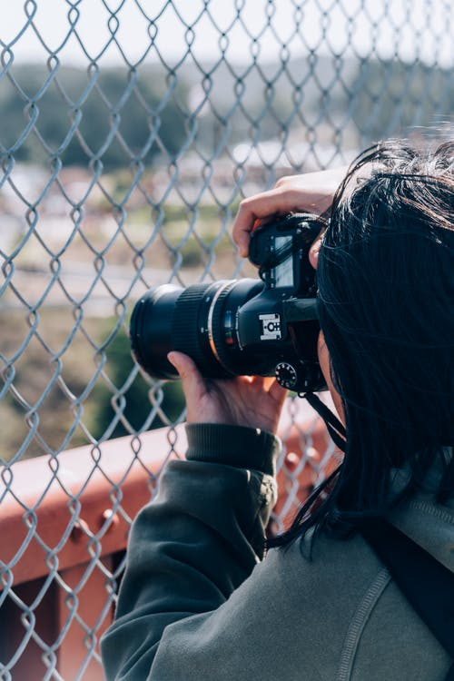 Woman Holding Dslr Camera Taking A Photo Behind A Wire Mesh Fence