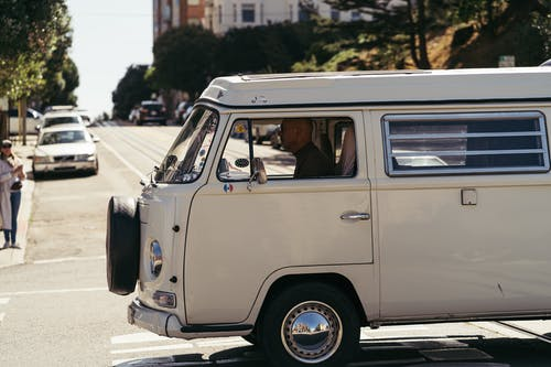 Man Driving An Old White Volkswagen  Kombi