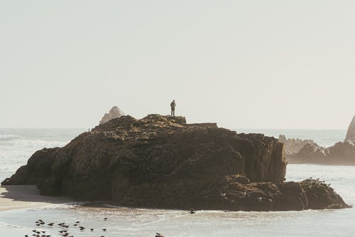 Person Standing on Rock Formation By The Seashore