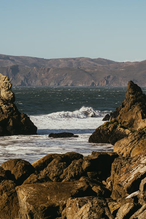 Scenic View Of The Sea Surrounded By Rocky Hills And Mountains