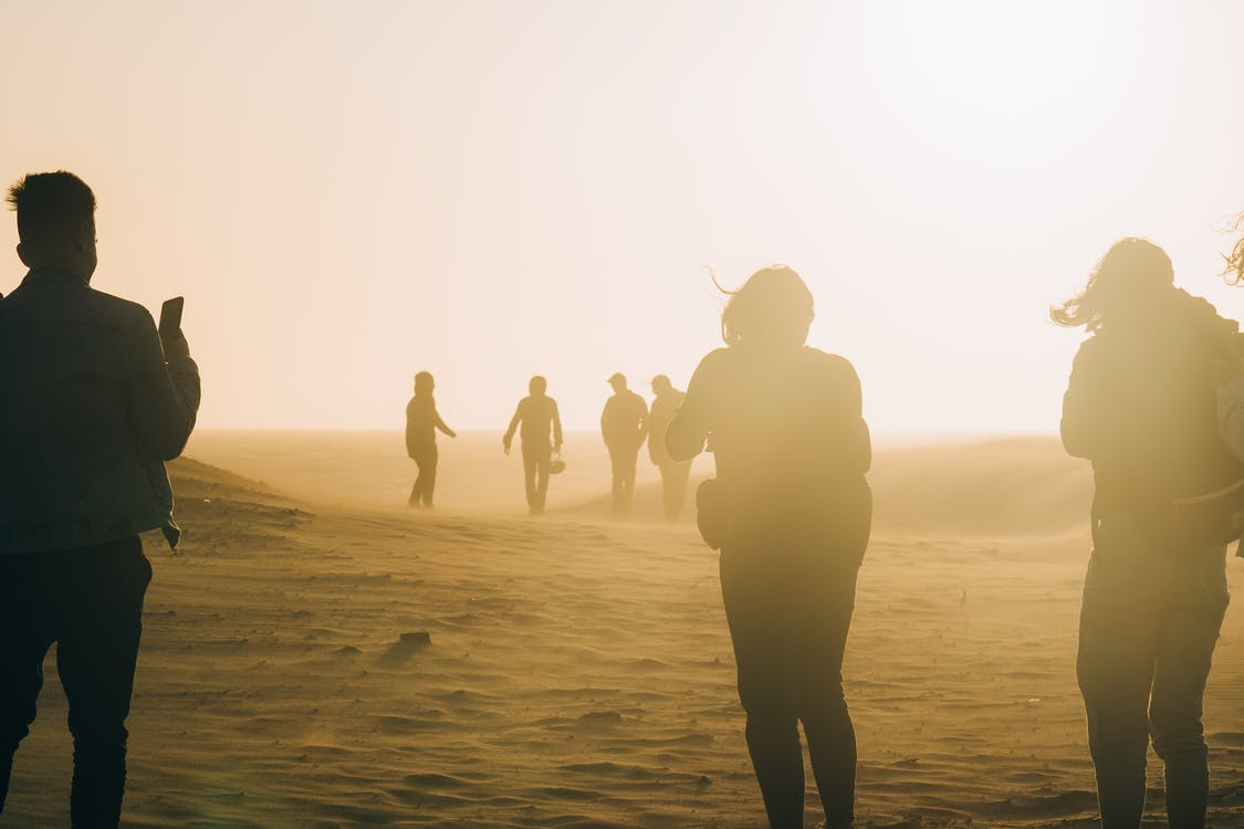 People Walking on Desert On A Windy Day With Dust Clouding Around Them