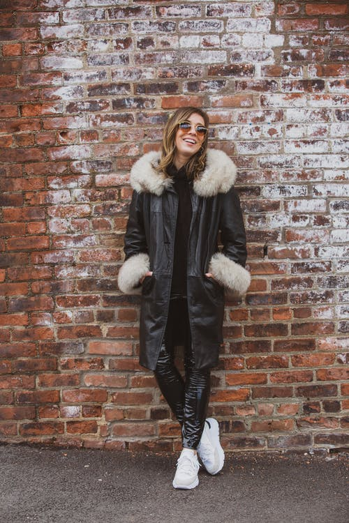 Laughing Woman Wearing Black Coat And Sunglasses Standing Against The Wall