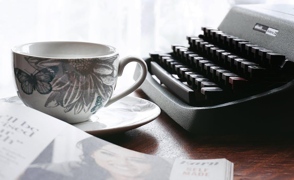 Taza Y Platillo De Cerámica Floral Blanco Y Gris Cerca De La Máquina De Escribir Y El Libro Negros