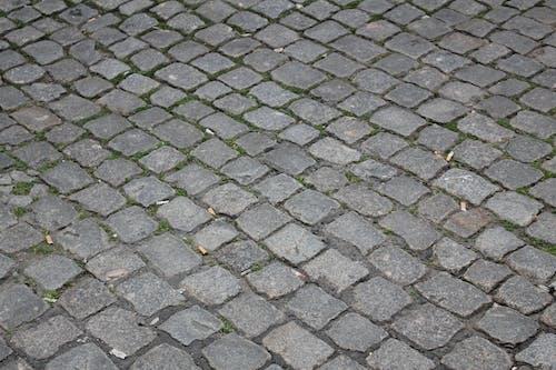 Free stock photo of cigarette butt, cobblestone street, cobblestones