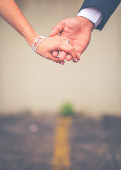 Photo of Man and Woman Holding Hands