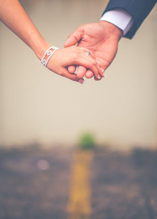 Kostenloses Stock Foto zu braut und bräutigam, frau, händchen halten, hände