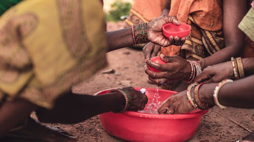 People Washing Their Hands in a Round Red Plastic Container