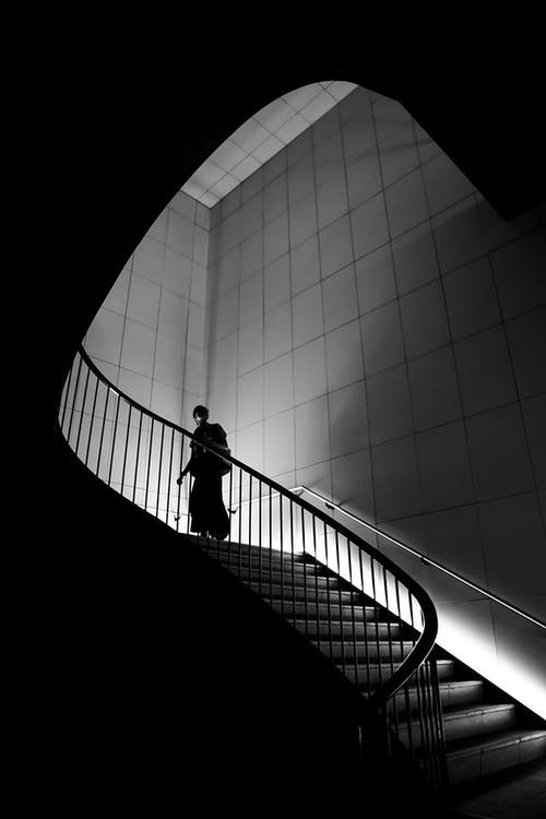 Person Walking On Stairs In Greyscale Photograph