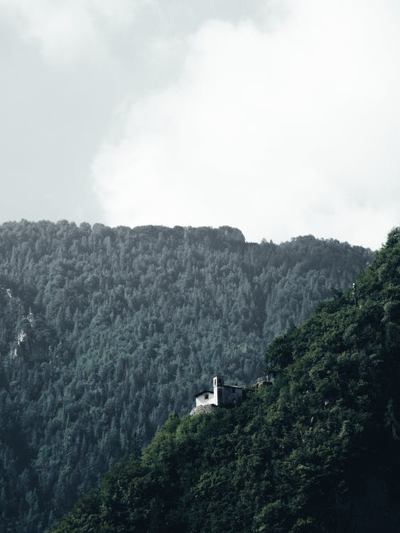 Aerial Photography Of A House On The Edge Of A Mountain Forest Under White Sky