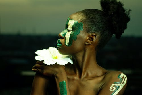 Topless Woman With White and Green Paint on Face Glancing Her Right Side
