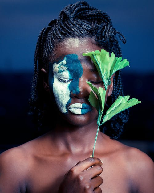 Woman With Paint On Face Holding Faux Leaves