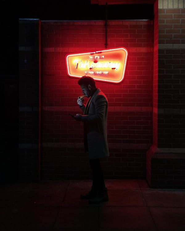 Silhouette of Person Standing Near A Neon Light Signage