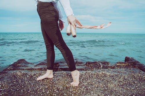 Darmowe zdjęcie z galerii z boso, czarne spodnie, morze, na palcach