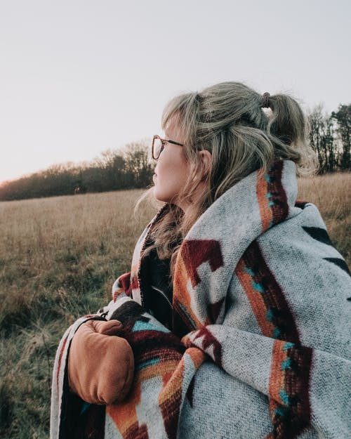 Woman Wrapped In A Printed Wool Blanket And Mittens Out In The Grass Field