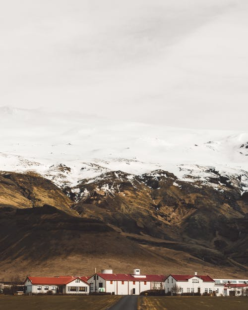 A Small Town On The Foot Of Snow Capped Mountains