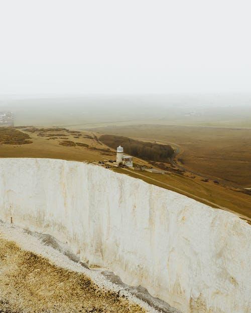 White Concrete Lighthouse On The Edge Of A Mountain Cliff