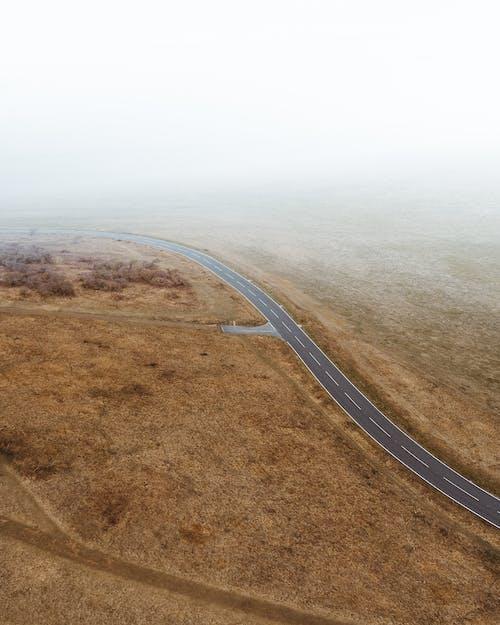 Asphalt Road Between Brown Field