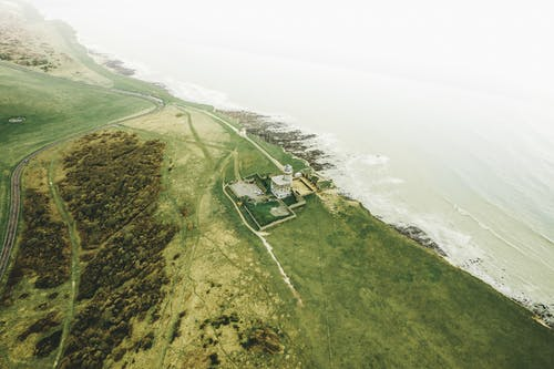 Aerial View Of A Lighthouse By The Cliff Of A Plateau With Lush Vegetation