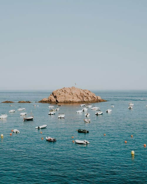 An Offshore Rock Formation Surrounded By Speedboats