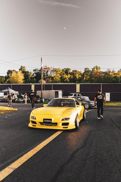 Man Walking Beside A Yellow Sports Car