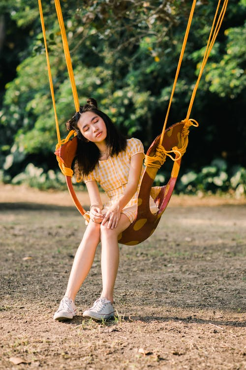 Photo of Woman Sitting on Swing Chair
