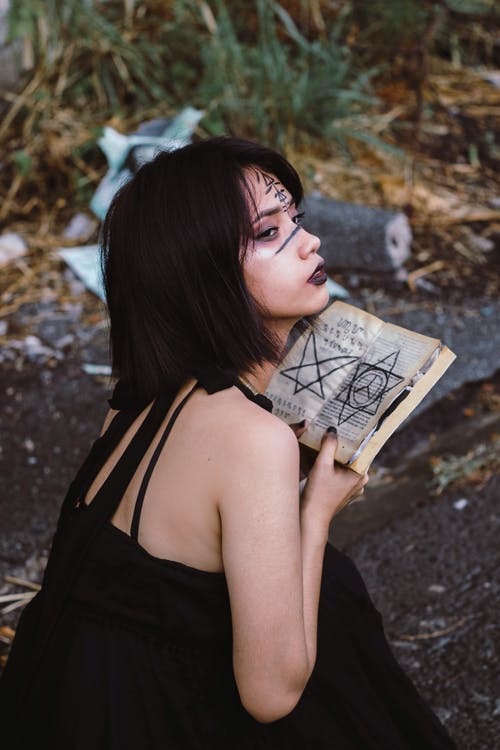 Woman Wearing Black Sleeveless Top While Holding Book