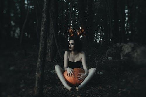 Woman In Black Dress Holding A Pumpkin