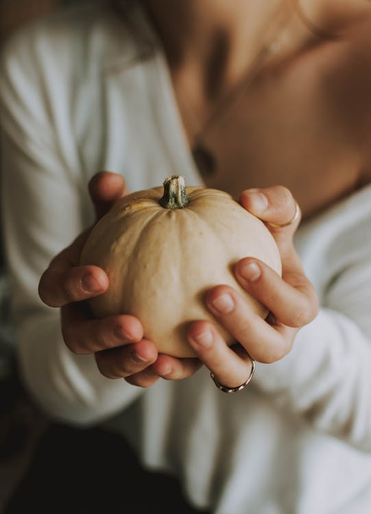 Woman Holding Pumpkin With Both Hands
