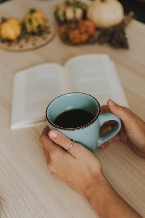 Person Holding Mug of Coffee Beside an Open Book