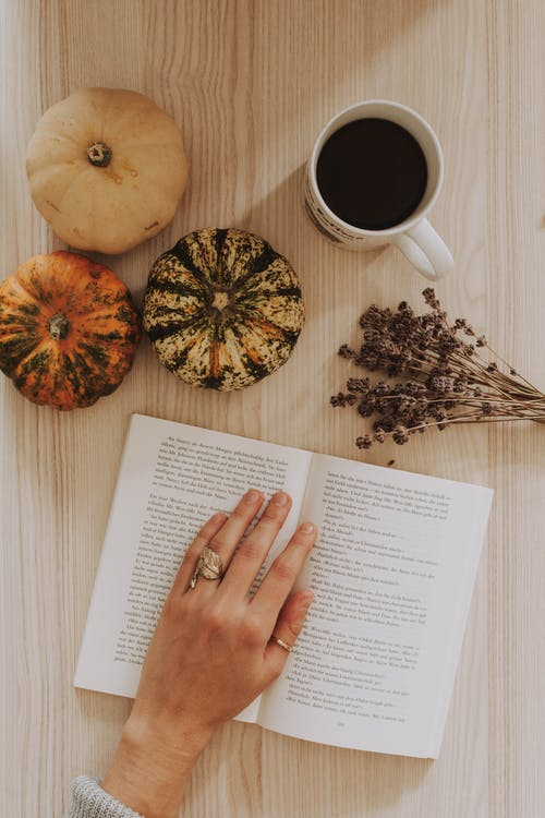 Top View Of A Woman's Hand On A Book Beside A Coffee Mug On A Table