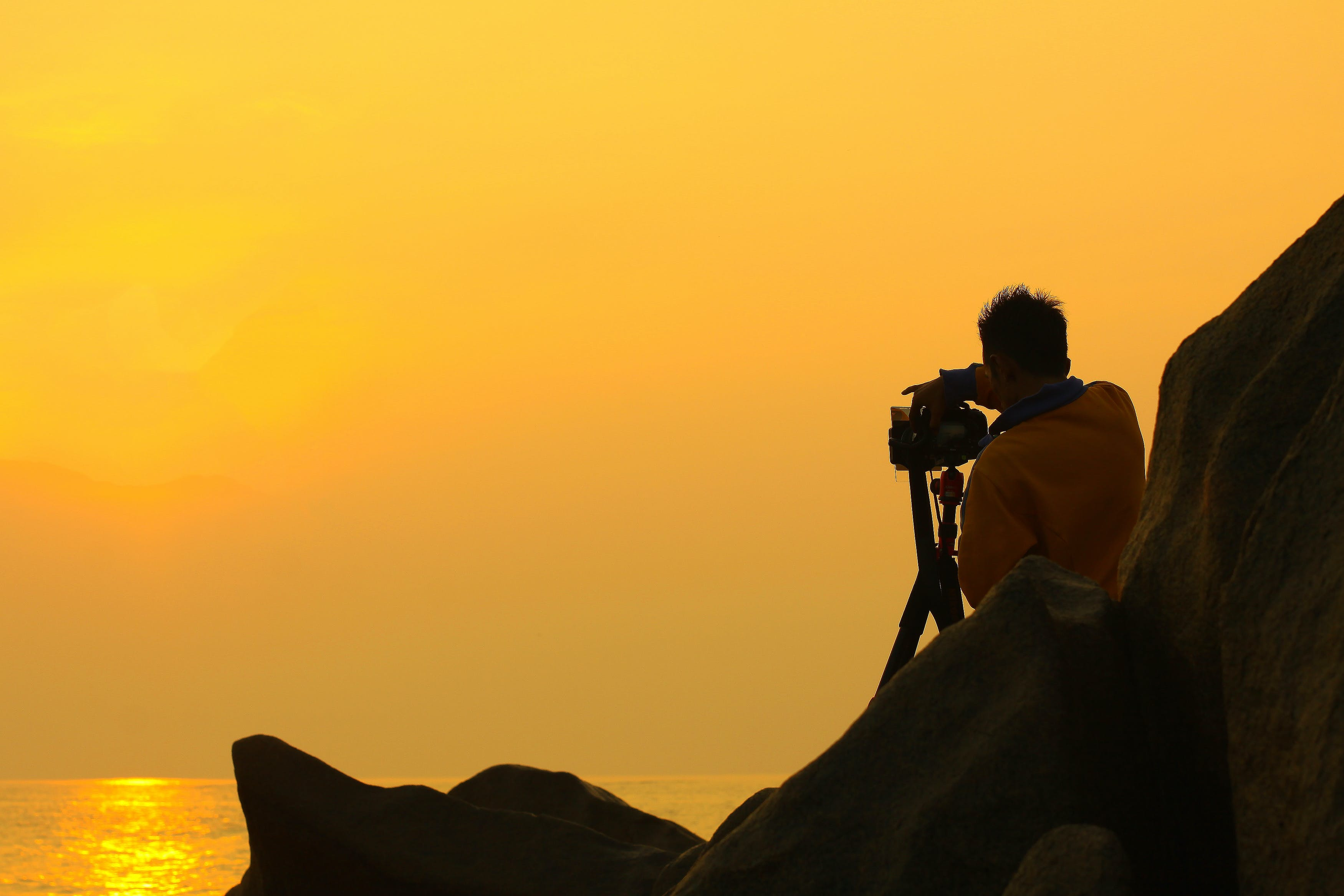 Man Holding Dslr Camera during Golden Hour