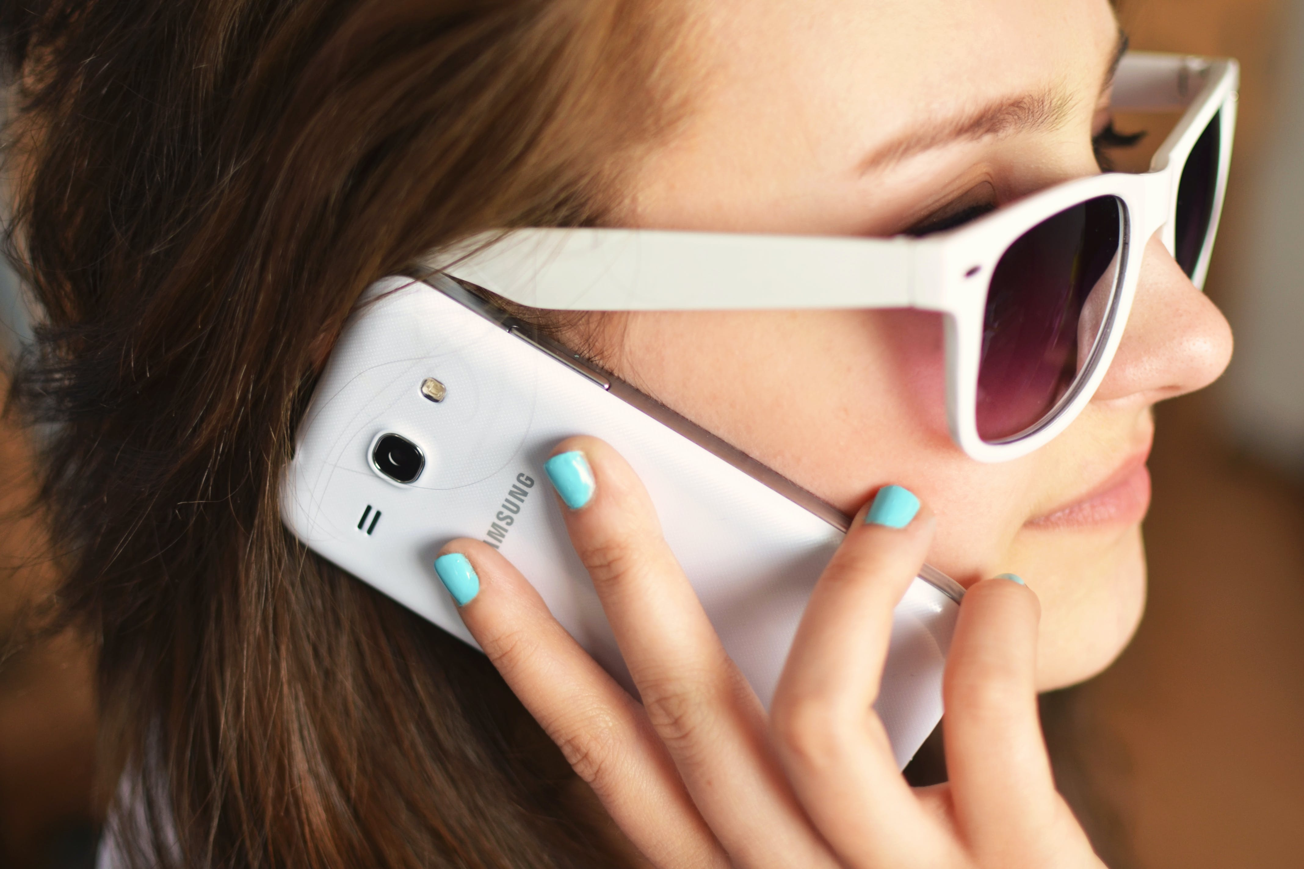 Smiling Woman Wearing Sunglasses While Talking on White Samsung Smartphone