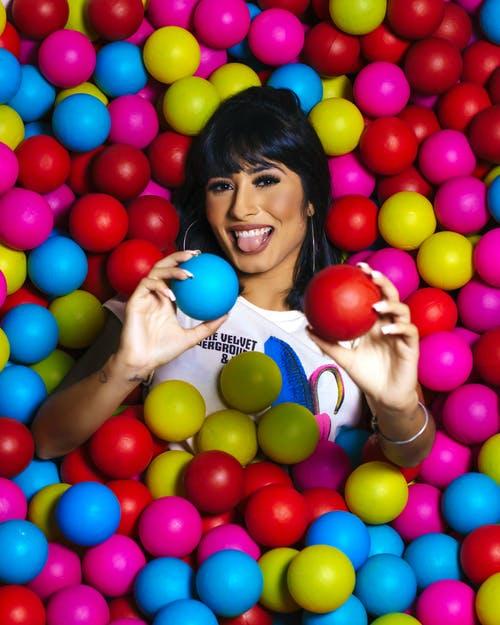 Photo of Woman Surrounded by Multicolored Balls