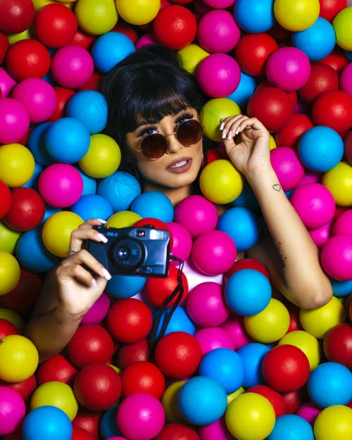 Photo Of Woman Laying On Assorted-Colored Balls
