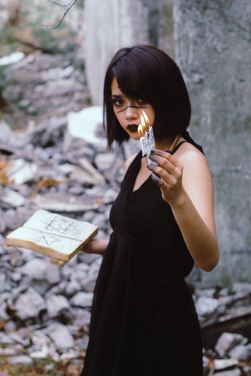 Woman Wears Black Sleeveless Dress Holding Book