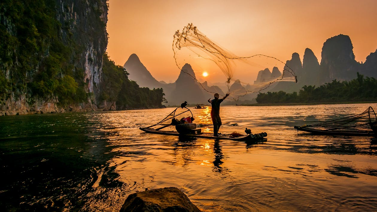Person's on Boat Throwing Fishing Net