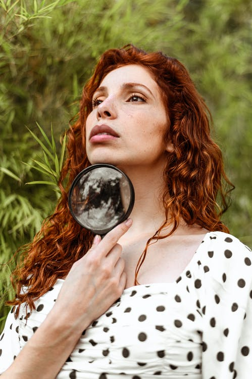Woman Holding Black Framed Magnifying Glass