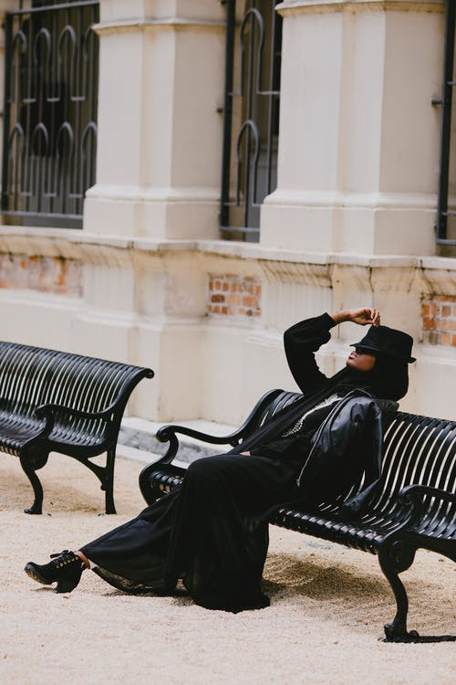 Woman in Black Leather Jacket Sitting Black Metal Bench