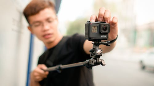Man Holding Monopod With Action Camera